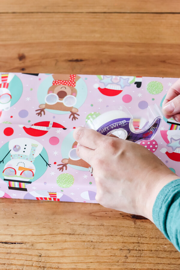 woman's hand holding tape on wrapping paper on box
