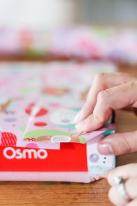 woman's hand folding corners of wrapping paper on box