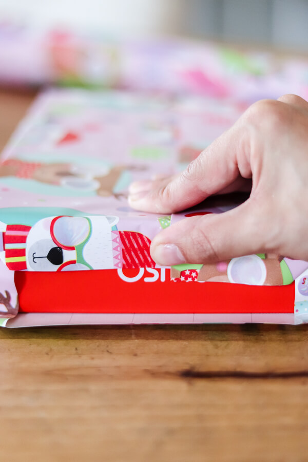 woman's hand folding ends of wrapping paper on box