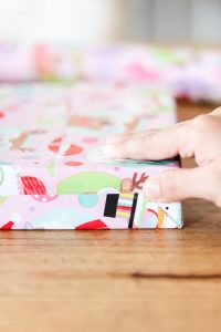 woman's hand taping ends of wrapping paper on box