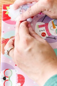 taping mini christmas ornament gnome onto pink wrapping paper