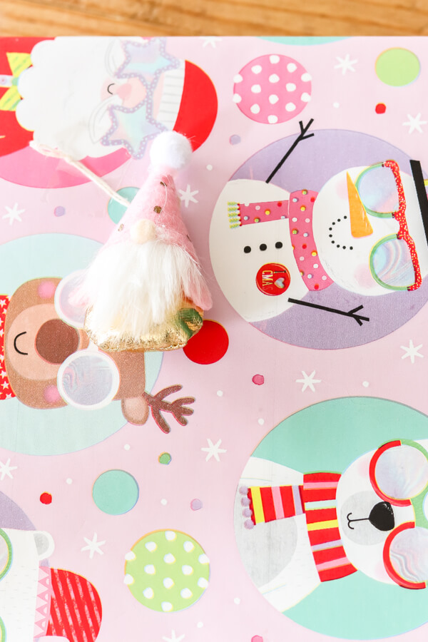 mini gnome ornament on pink Christmas wrapping paper