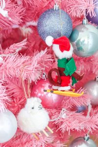 closeup of little sheep and monkey on skis ornament on pink Christmas tree