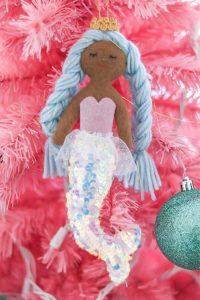mermaid with brown skin and blue hair on pink Christmas tree