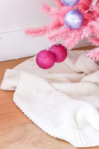 2 sparkly pink Christmas ball ornaments hanging on pink Christmas tree