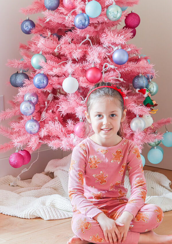 little girl in ponytail and gingerbread pajamas sitting in front of decorated Pink Christmas tree
