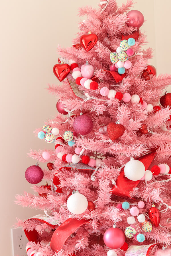 closeup of pink Christmas tree with red, white, and pink pom garland and red heart ornaments, pink glitter ornaments and white ornaments