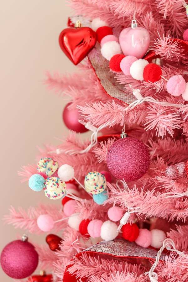 closeup of pink Christmas tree with red, white, and pink pom garland and pink glitter ornaments ornaments