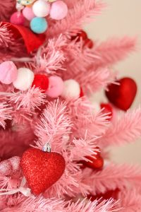 closeup of pink Christmas tree with red, white, and pink pom garland and red heart ornaments