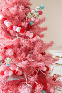 closeup of pink Christmas tree with red, white, and pink pom garland and cupcake picks