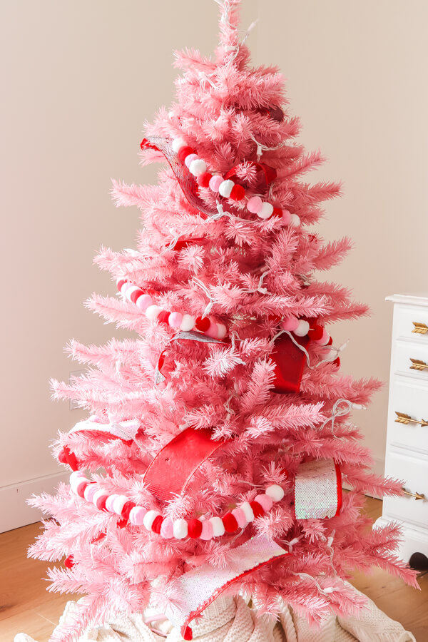 Pink Christmas tree with red sequin ribbon and red, white, and pink pom garland