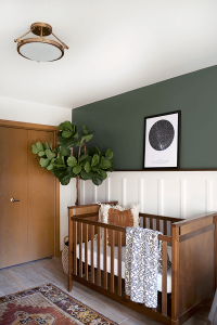 white board and batten wall with hunter green painted wall with wood crib and wood door