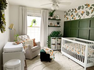 dark green nursery feature wall with clementine wallpaper and white crib