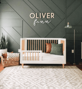 hunter green nursery feature wall with name above a white and wood crib