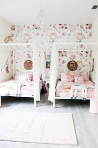 2 white canopy beds with name signs and pink bedding