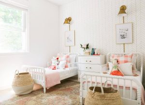 2 white twin beds with dresser in between and vintage rug with white and gold striped wallpaper