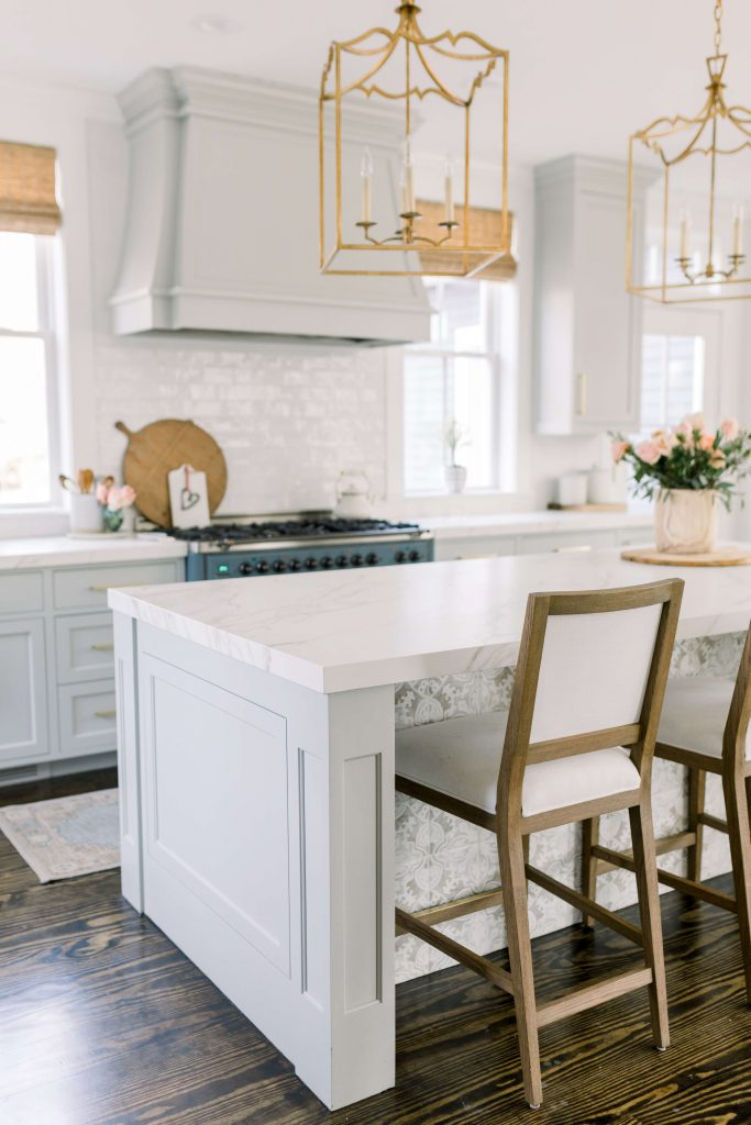 grey kitchen cabinets with white countertops and gold fixtures