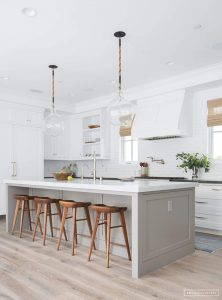 white kitchen with gray island and brown wood bar stools