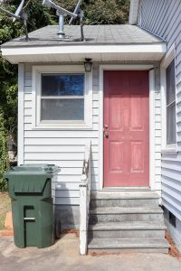 side home entrace with red door and green trash can