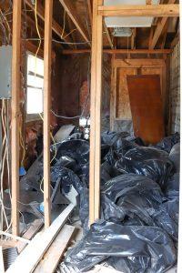 interior home framing and black trash bags