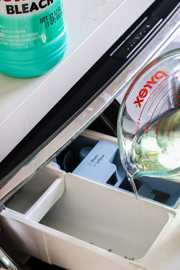glass pyrex cup pouring vinegar into top of front load washing machine