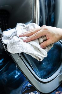 woman's hand wiping inside door of front load washing machine