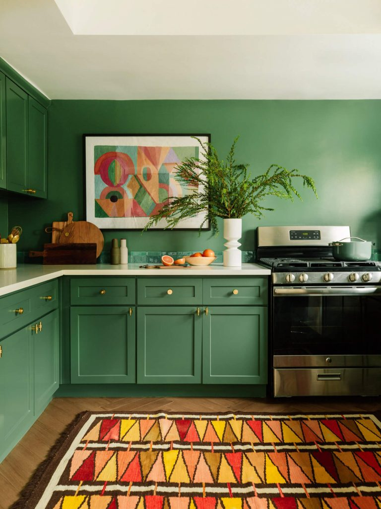 jewel tone green kitchen cabinets with bold geometric accent rug
