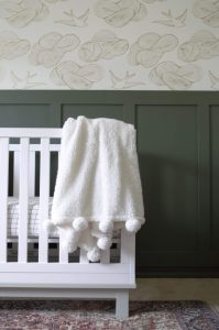 dark green board and batten wall with wallpaper and white crib