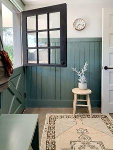 dark green board and batten wall with dark green dutch door