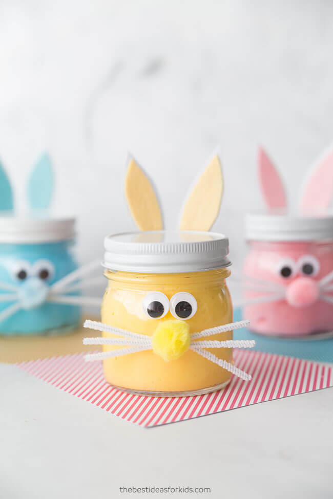 pink, yellow and blue slime in short mason jars decorated to look like bunnies