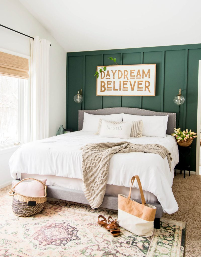 dark green bedroom accent wall with white bedding and tan accents