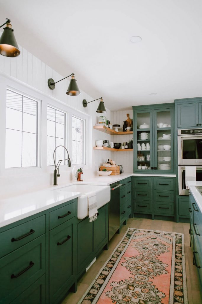 dark green paint kitchen cabinets with white countertops and vintage runner rug