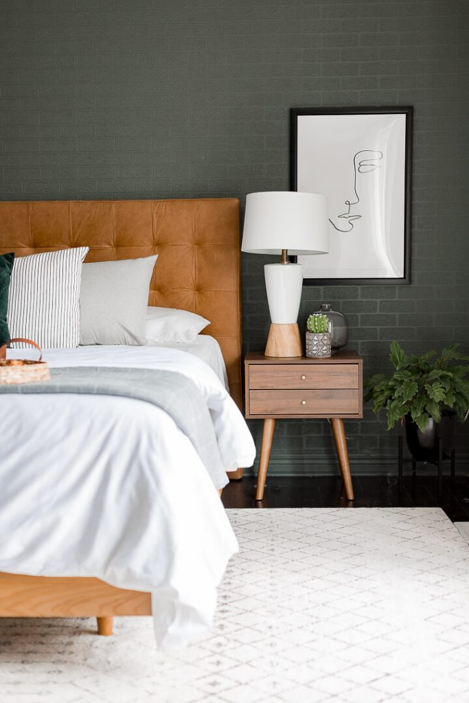 dark green bedroom accent wall with medium brown leather headboard and white bedding