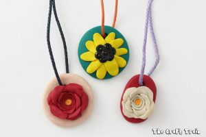 3 polymer clay flower necklaces on a white background