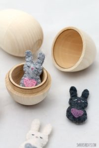 tiny grey and black easter bunnies in wooden eggs