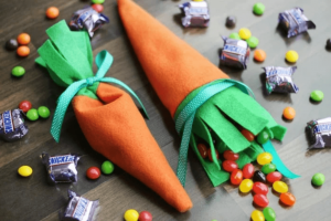 felt carrots on a dark background with candy coming out of them and snickers bars around them