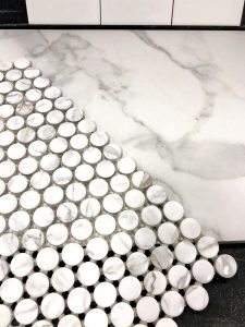 closeup of white marble tile with grey veining and white and grey penny tile