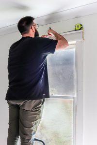 man in black tshirt measuring width of window
