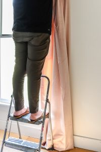 man standing on step stool holding up curtain panel
