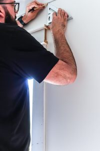 man in short sleeve black shirt holding up speed square marking wall with a pencil
