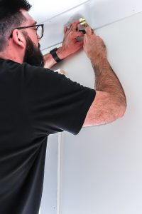 man in black shirt and glasses using pencil to mark inside of curtain rod bracket