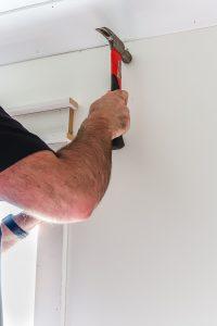 man in black short sleeve shirt holding a hammer