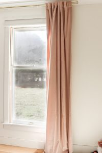 single blush curtain panel hanging on curtain rod