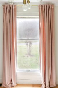 blush velvet curtains hanging on a gold curtain rod