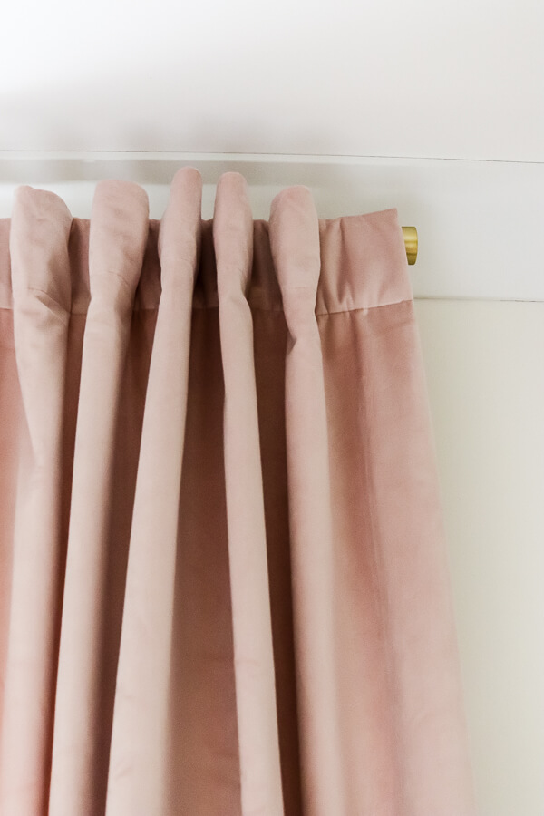 top of blush pink velvet curtain panels and gold curtain rod