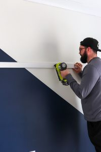 man with hat using Ryobi nail gun attaching board and batten to the wall