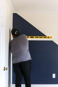 man in gray shirt and hat with yellow level installing board and batten on a wall