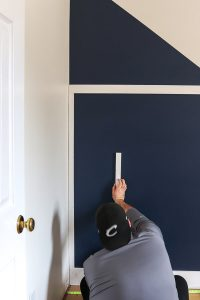 man in backwards black hat sitting on the floor installing board and batten on a navy accent wall