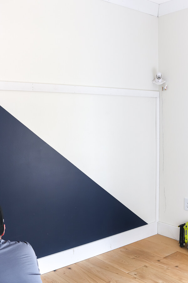 navy diagonal accent wall with baby monitor camera in the corner