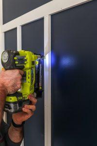 man with ryobi nail gun creating a board and batten feature wall